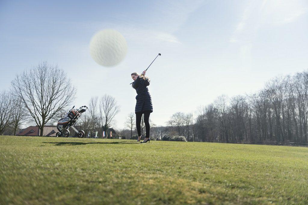 Vrouw slaat golfbal op golfbaan