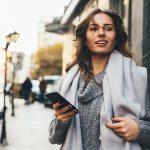Jonge vrouw op straat met smartphone.